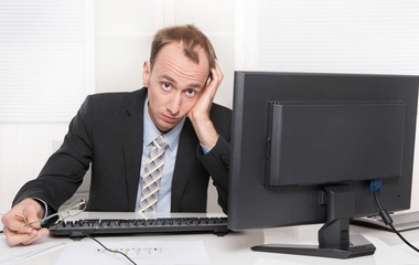 Frustrated employee sitting and desk holding his head - problems and stress at work